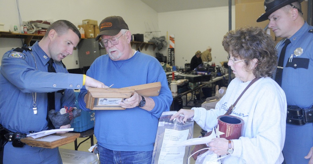RECOVERED: State police Troopers Aaron Turcotte, left, and Bill Plourde help Henry and Andrea Trefethen inventory items they found Wednesday at the Kennebec County Sheriff's Office in Augusta. Hundreds of stolen pieces of property recovered from a Wayne burglary ring were returned to victims. Several household items from the Trefethens' camp on Parker Pond in Fayette were discovered in the loot seized by deputies and troopers.
