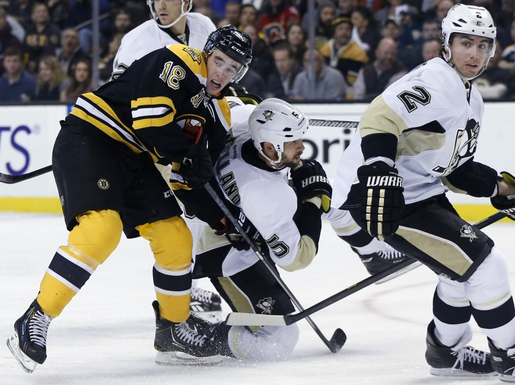 Boston Bruins right wing Reilly Smith (18) battles Pittsburgh Penguins defenseman Deryk Engelland (5) for position as Penguins defenseman Matt Niskanen (2) looks on in the second period of an NHL hockey game in Boston, Monday, Nov. 25, 2013. (AP Photo/Elise Amendola)