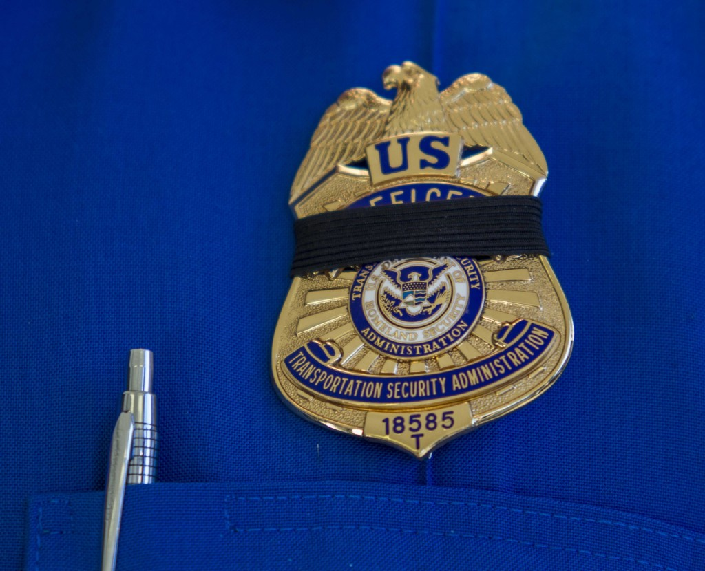 A Transportation Security Administration employee wears a black ribbon over his badge on Saturday, Nov. 2, 2013, in Los Angeles International Airport. A gunman armed with a semi-automatic rifle opened fire at the airport on Friday, killing a Transportation Security Administration employee and wounding two other people in an attack that frightened passengers and disrupted flights nationwide.