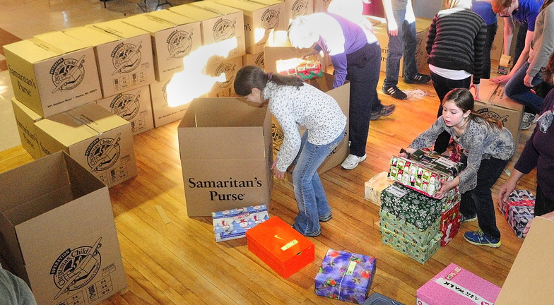 Giving: Mary Farrar, bottom right, and other volunteers from a church group from Peru put shoe boxes of gifts into shipping boxes on Saturday at Penney Memorial Baptist Church in Augusta. Pam Cullen said that there had been about 1,500 shoe boxes dropped of by Saturday and that more were expected to come in before they're shipped out Monday morning. The Operation Christmas Child is a project of the Samaritan's Purse and boxes will be distributed around the country and world.