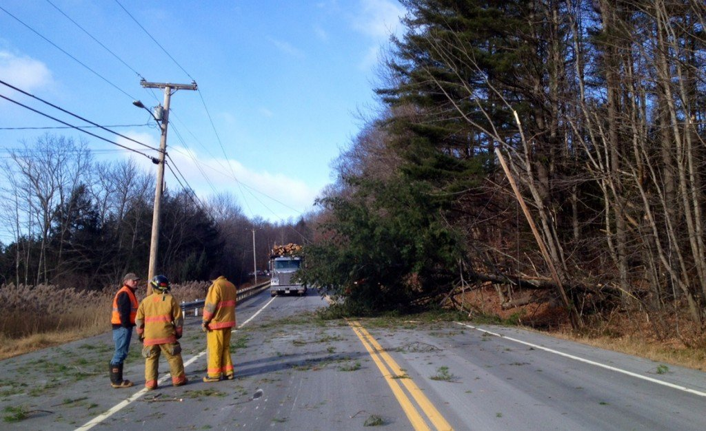 A crew from the Moscow Fire Department stands by a downed tree and guide wires that were blocking both lanes of traffic on Route 201 in Moscow Sunday morning.