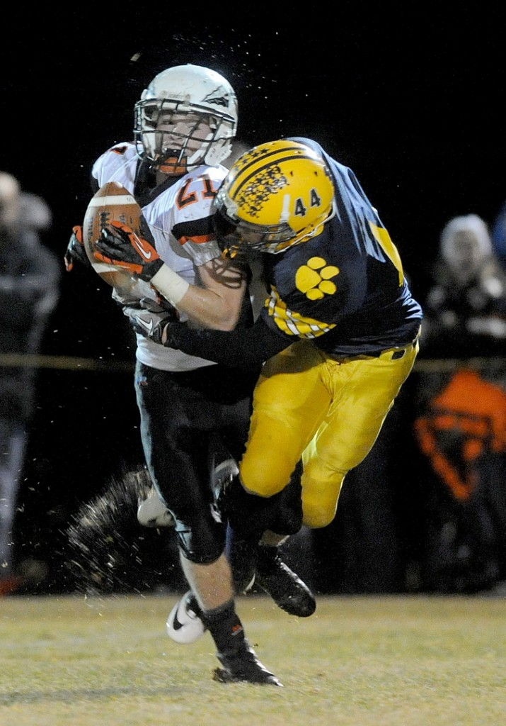 Staff photo by Michael G. Seamans Skowhegan Area High School's Ben Salley, 21, makes a catch as he is hit by Mt. Blue High School defender Nathan Pratt-Holt, 44, in the second quarter in Farmington on Saturday.
