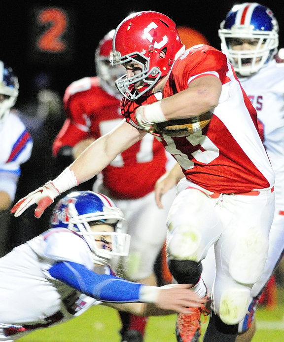 Staff photo by Joe Phelan Cony running back Reid Shostak, right, avoids a diving tackle by Messalonskee defensive back Jake Dexter during a game on November 8, 2013 at Alumni Field in Augusta.