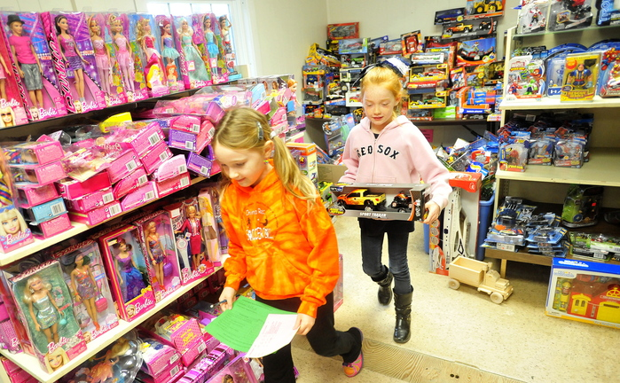 GIFT GIVING: Alexis Rancourt, 8, left, and Lauren Tyler, 8, both third-graders at China Primary School, help pack gift boxes for poor area children at the Maine Children's Home for Little Wanderers on Tuesday.