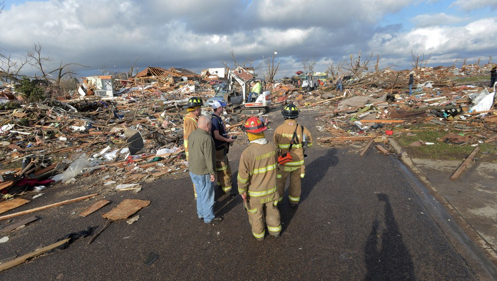 Firefighters stand in a Washington, Ill., neighborhood flattened by a tornado on Sunday. The tornado, one of dozens that rampaged across the Midwest, tore from one end of town to the other, toppling power lines, rupturing gas lines and ripping off roofs.