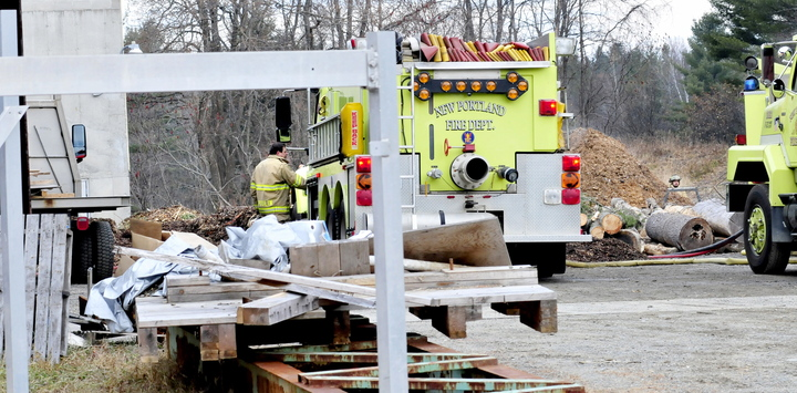 CLOSE CALL: New Portland Fire Chief Kip Poulin speaks with firefighters as piles of wood chips are taken out of JR Fabricating business on Sunday. Poulin said there was a fire earlier in the wood furnace system that brought several departments and firefighters to the scene off the River Road.