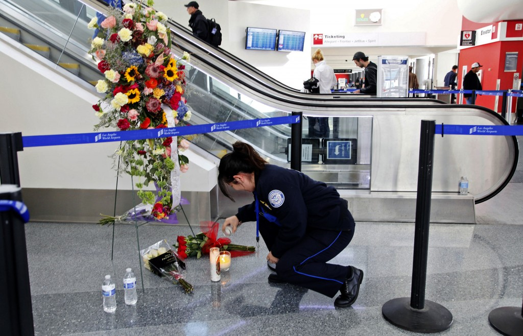 Transportation Security Administration Officer Alexa Mendoza lights a candle at a memorial to TSA officers killed and wounded at Terminal 3 at Los Angeles International Airport on Monday. TSA Officer Gerardo I. Hernandez was killed and two officers and one civilian wounded in the shooting at Terminal 3 on Friday.