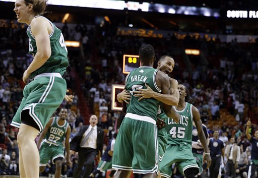 Boston Celtics' Jeff Green is hugged by Avery Bradley after shooting a game-winning three-point basket against the Miami Heat during the second half of an NBA basketball game, Saturday in Miami. The Celtics won 111-110. At left is Celtic's Kelly Olynyk.