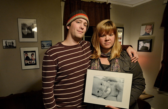 """Nick Bowie-Haskell and Nicole Wheeler hold a photograph of their son Charlie in their home in South Portland on Nov. 25. The couple have started a fundraising campaign called """"17 Days of Charlie"""" in their son's memory. Proceeds will benefit another family and the Maine Children's Cancer Program."""