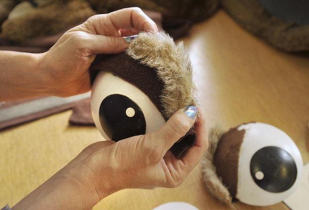 Colleen Writt replaces the eyebrows on a mascot costume undergoing a few repairs at her shop.