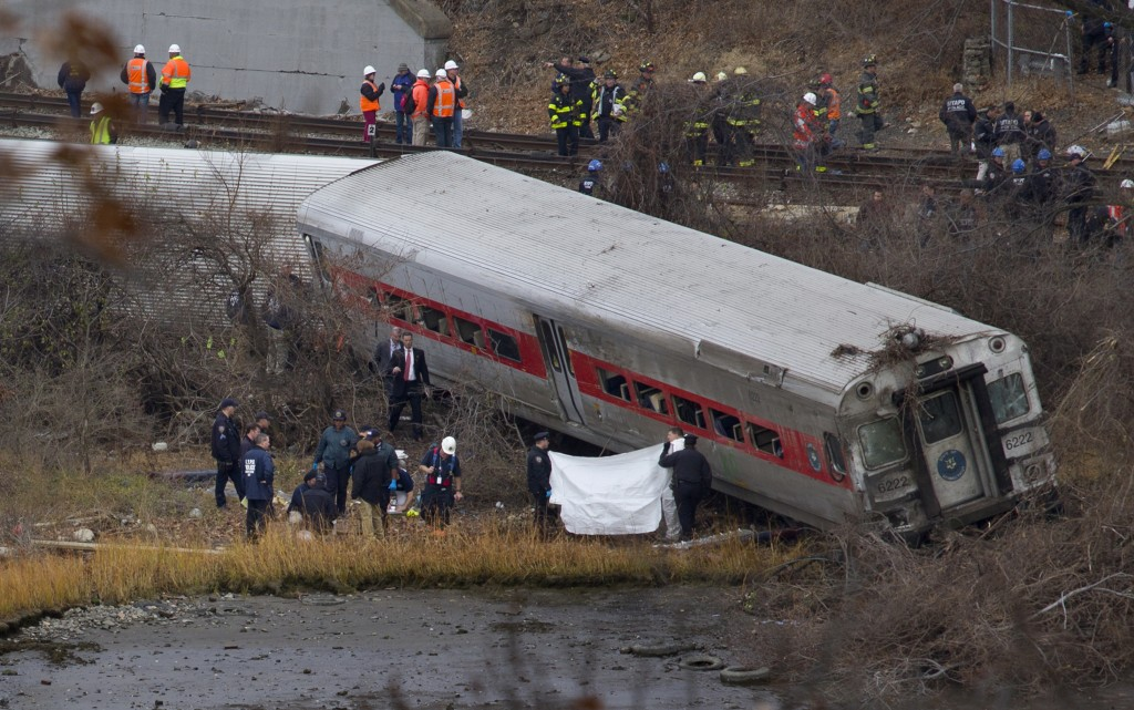 Viewed from Manhattan, first responders and others work at the scene of a derailed Metro-North passenger train in the Bronx borough of New York on Sunday. The train derailed on a curved section of track in the Bronx, coming to rest just inches from the water, killing at least four people and injuring more than 60, authorities said. Police divers searched the waters to make sure no passenger had been thrown in, as other emergency crews scoured the surrounding woods.