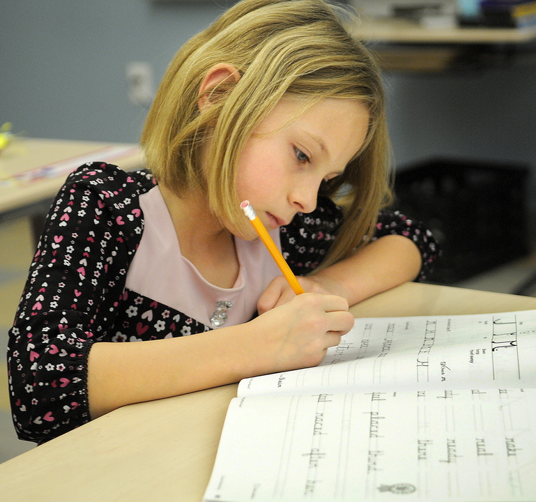 CURSIVE: Chelsea Elementary third-grader Chloe Smiley works on a cursive lesson during a recent class.