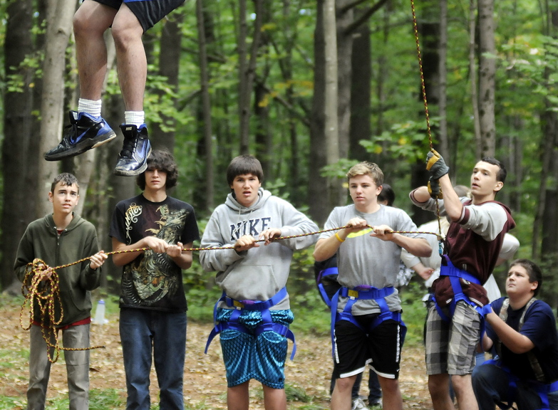 COMING DOWN: Cony High School students help a classmate descend from the catwalk at the school's rope course in Augusta. The physical education class emphasizes cooperation instead of competition.