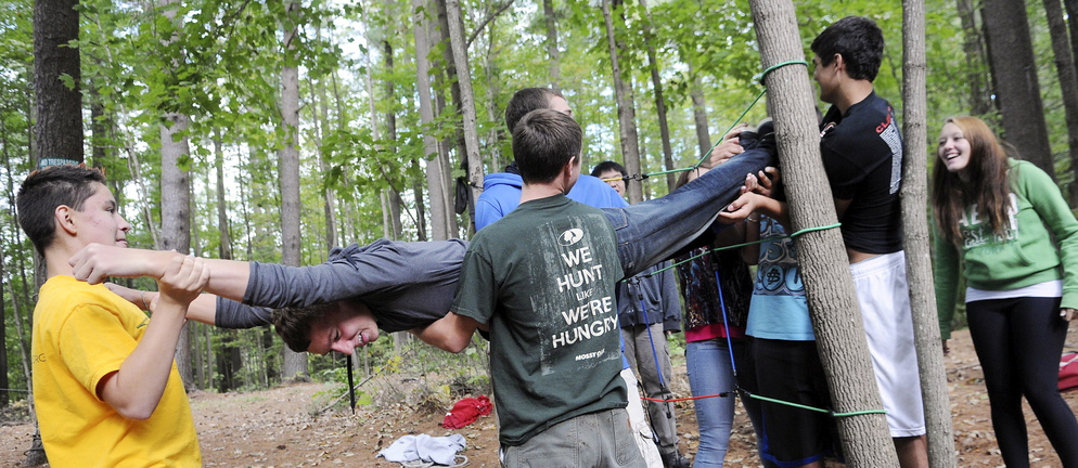 HELPING HANDS: Cony High School student Noah Guerrette is carried through ropes on the spider pull earlier this year at the school's rope course in Augusta. The physical education class emphasizes cooperation instead of competition.