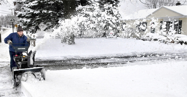 BYE BYE SNOW: Louie Barnes clears his driveway of several inches of snow in Waterville on Monday.