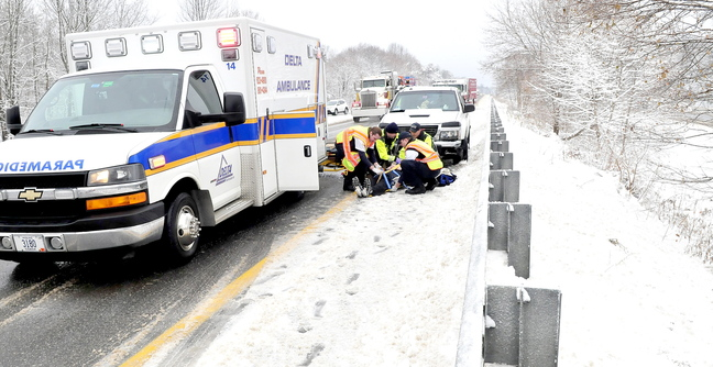 SLIP SLIDING: Emergency workers prepare to transport an injured person after a pickup truck collided with a car in the southbound lane of Interstate 95 in Waterville on Monday.