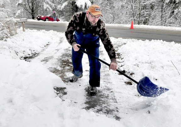 WINTER WOES: Don Gardner clears his driveway in Sidney as motorist Lydia Williams, in background, waits for a tow truck after her car slid off the snow-covered West River Road on Monday.