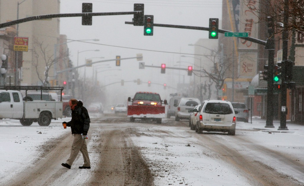 Cars and pedestrians creep along slick, snow-covered streets on Tuesday in downtown Casper, Wyo. Winter storm warnings and advisories had been posted for all but the extreme western part of the state Tuesday.