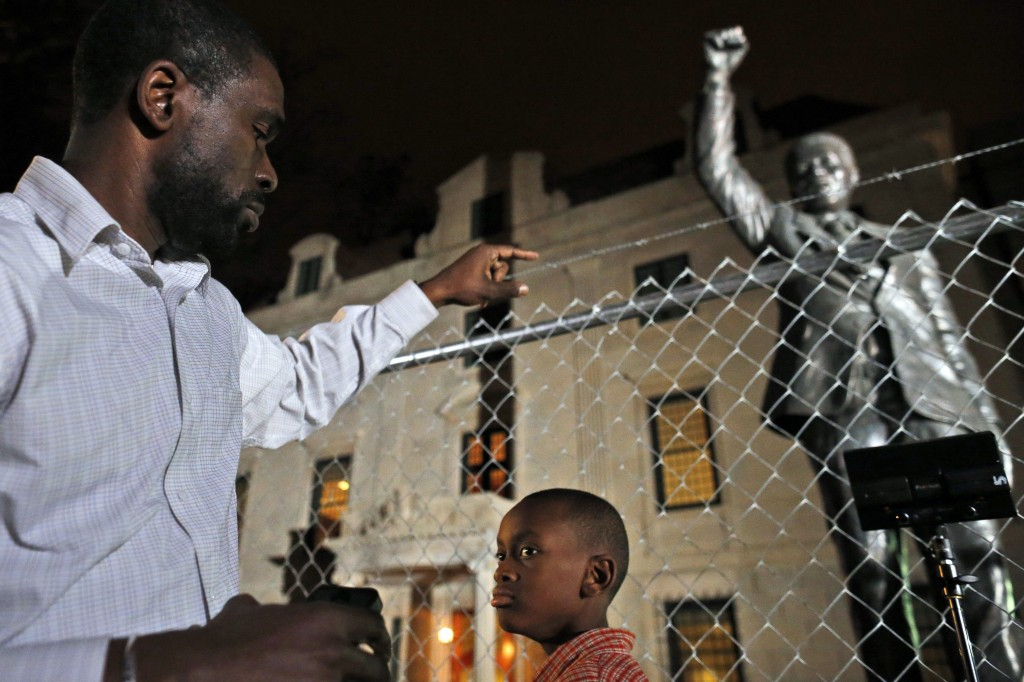 Dijon Anderson of Bowie, Md., and his son Keaton, 10, visit the statue of Nelson Mandela at the South African Embassy in Washington, which is currently under renovation, Thursday, Dec. 5, 2013. Mandela, former President of South Africa and anti-apartheid icon, died earlier Thursday at 95.