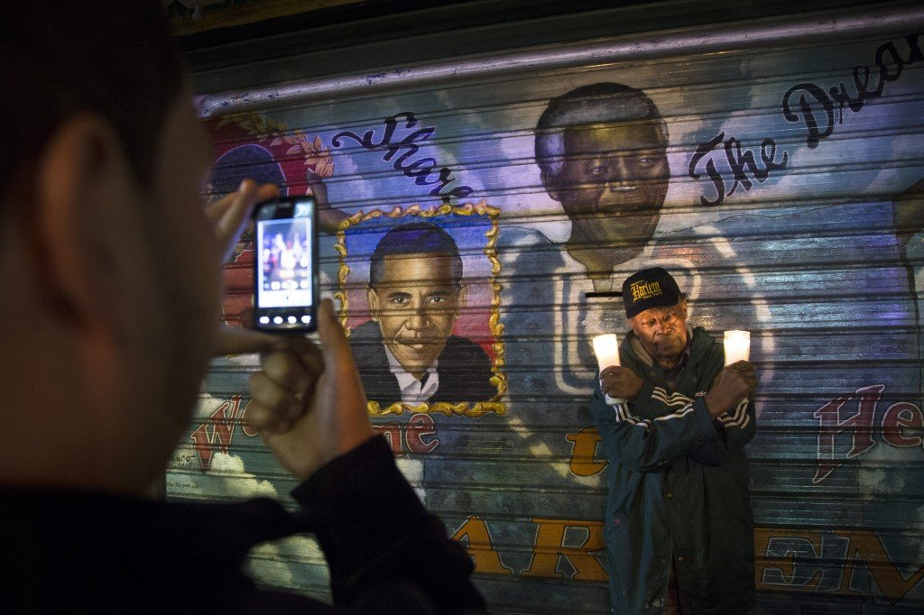 "A man takes a picture of an artist who goes by the name ""Franco the Great"" in front of a mural of South African leader Nelson Mandela that the artist painted in 1995, and later added U.S. President Barack Obama, on 125th Street in the Harlem neighborhood of New York, Thursday, Dec. 5, 2013. Mandela, South Africa's first black president, died Thursday after a long illness. He was 95."