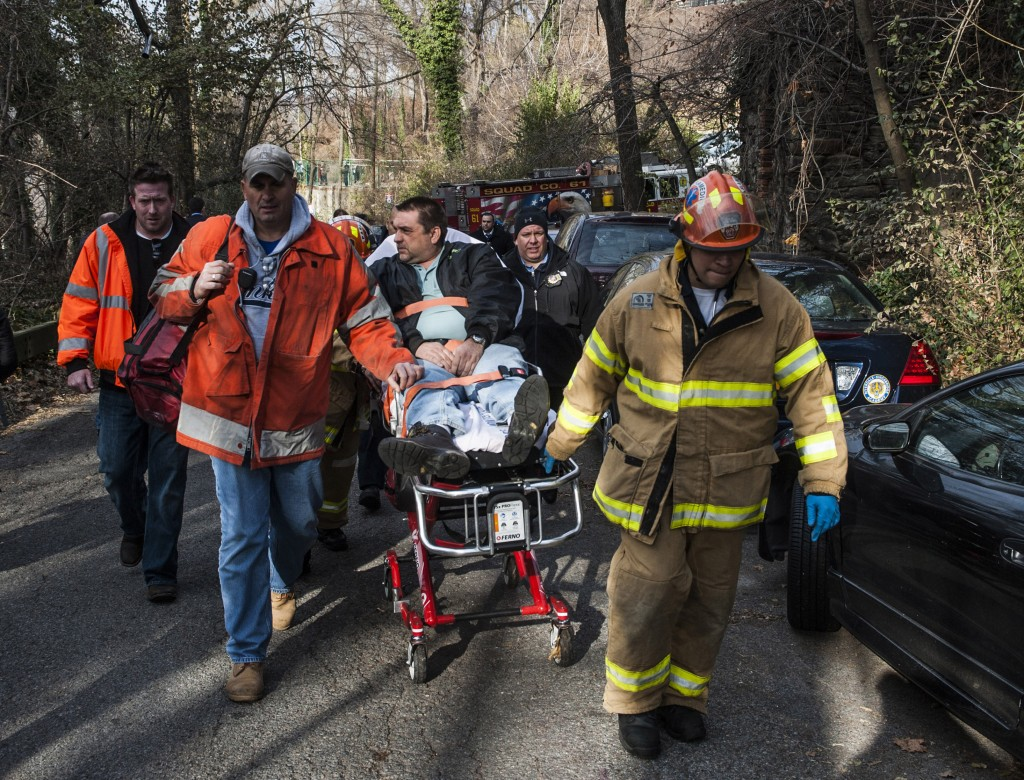 In this photo taken on Sunday, Metro North Railroad engineer William Rockefeller is wheeled on a stretcher away from the area where the commuter train he was operating derailed in the Bronx.