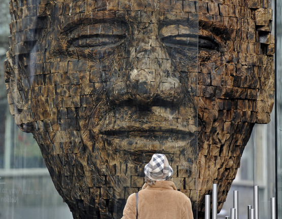 """A woman views a new giant wooden sculpture of former South African President Nelson Mandela in the city center of Essen, Germany, in this Feb. 23, 2011 file photo. The artwork """"Mandela, 2700 pieces of Life's history"""" by artist Jems Robert Koko Bi from the Ivory Coast is made of burned spruce wood and symbolizes the fight for freedom. On Thursday, Dec. 5, 2013, Mandela died at the age of 95."""