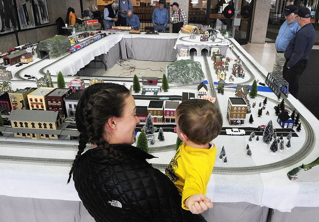 TRAIN GANG: Michelle Mosher and her son Alex Pelotte, 2, of Waterville, watch model trains go around the tracks Friday at the Maine State Museum in Augusta. The model railroad displays will be up and the museum will open free of charge from 10 a.m. to 3 p.m. today. The Great Falls Model Railroad Club and the Maine 3-Railers have set up and will operate a variety of displays running G, HO and O-gauge model trains and accessories. Go to kj.online for a video of the trains.