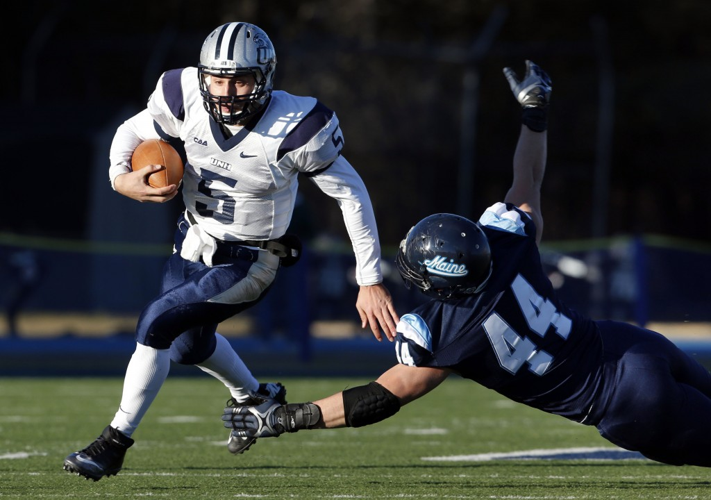 New Hampshire quarterback Sean Goldrich (5) scrambles past Maine defensive lineman Patrick Ricard (44) during the first half of an NCAA football playoff game, Saturday, Dec. 7, 2013, in Orono, Maine. (AP Photo/Robert F. Bukaty)