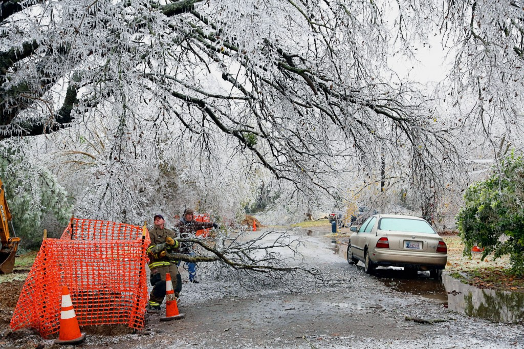 A Paris firefighter and a homeowner work together to clear debris from an ice storm in Paris, Texas, Friday, Dec. 6, 2013. A quarter of a million customers in North Texas were left without power, and many businesses told employees to stay home to avoid the slick roads. (AP Photo/The Paris News, Sam Craft)