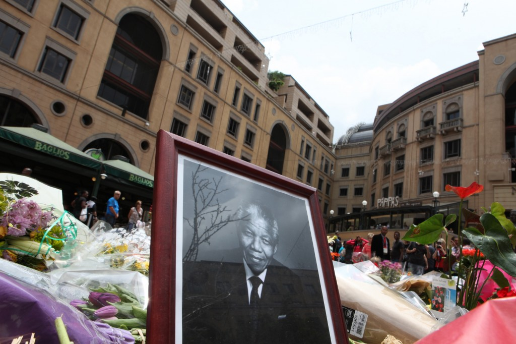 A portrait of former South African President Nelson Mandela is placed among a pile of flower tributes in Sandton, Johannesburg, South Africa, Saturday, Dec. 7, 2013. Mandela died Thursday at his Johannesburg home after a long illness. He was 95.