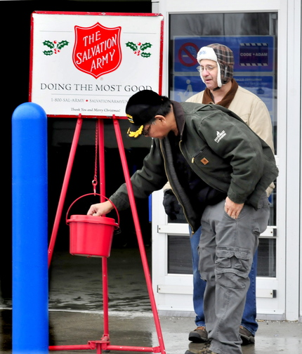 THANK YOU: Salvation Army volunteer Peter Wilson, right, watches as Jeff Cuares donates in Waterville earlier this week.