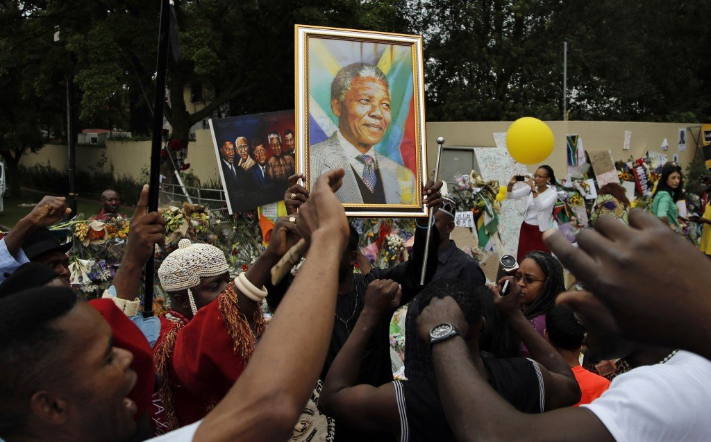 Mourners from Nigeria sing outside the home of Nelson Mandela in Johannesburg, South Africa, Monday. Tens of thousands are expected to attend the memorial service that is being staged in memory of the beloved leader.