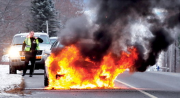 On fire: Fairfield Police Sgt. Paul St. Amand monitors a car that burst into flames on Norridgewock Road on Tuesday.