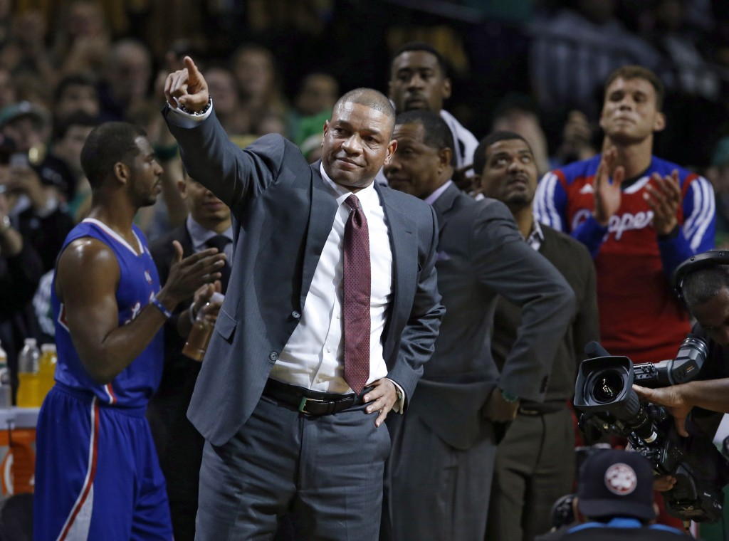 Current Los Angeles Clippers head coach and former Boston Celtics head coach Doc Rivers acknowledges fans during a video tribute to him in his first time back to the TD Garden after the first quarter of an NBA basketball game in Boston, Wednesday, Dec. 11, 2013. Applauding are Clippers Chris Paul, left, and Blake Griffin, far right. (AP Photo/Elise Amendola)
