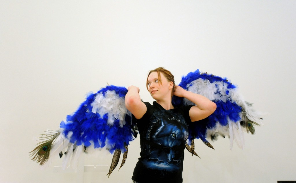 "Wings: Maeve-Wolf O'Reiley, 21, a sculpture student at the University of Maine at Farmington, tries on her prosthetic creation titled ""Flights of Fantasy"" during a set-up Wednesday for the campus exhibition. O'Reiley used more than 700 feathers and spent more than two weeks creating the winged prosthesis."