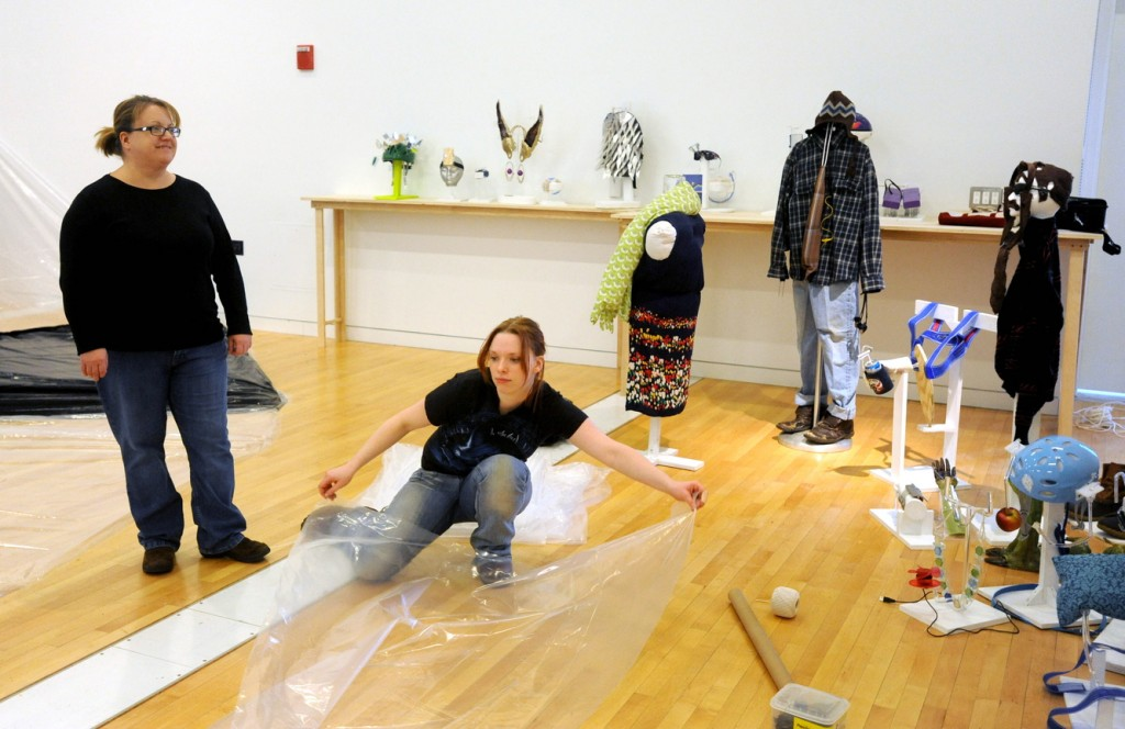 PROSTHESIS ART: Maeve-Wolf O'Reiley, center, and Jill Gingras, left, both sculpture students at the University of Maine at Farmington, prepare the Emery Arts Center for the prosthesis project on Wednesday. Students were challenged to create a prosthesis to overcome their own personal limitations.