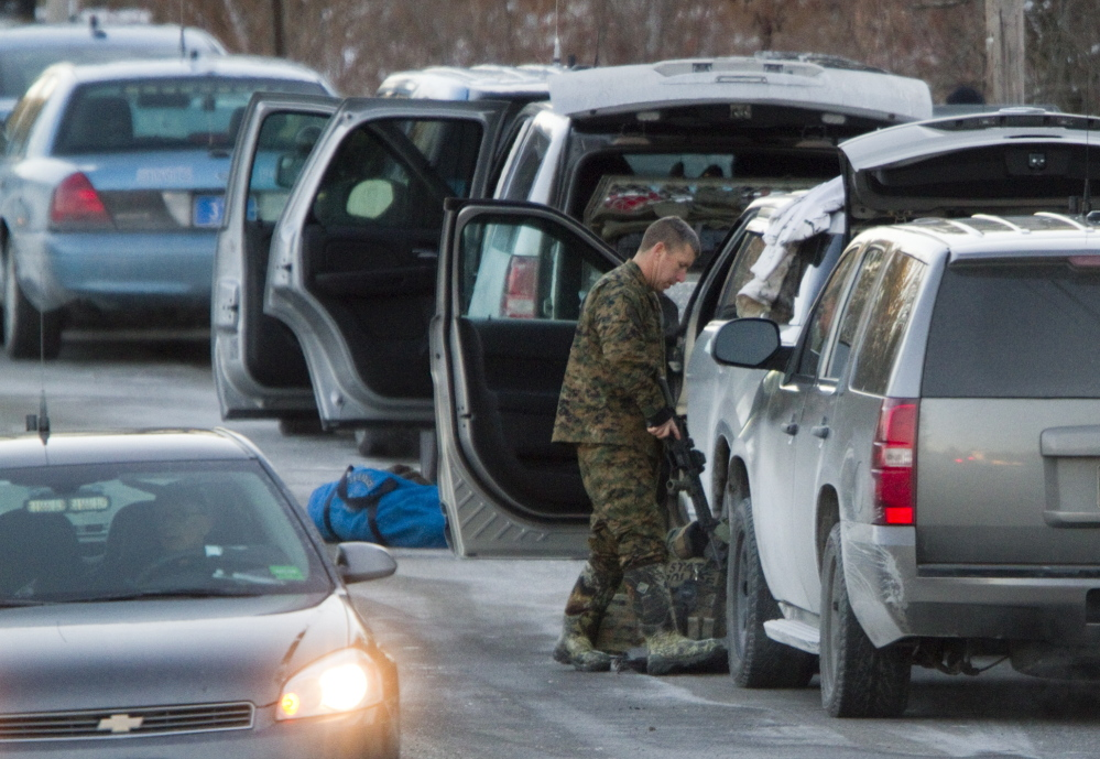 Carl D. Walsh/Staff Photographer A police officer wearing camouflage gear puts away his rifle after a standoff ended in a fatal shooting on Route 35 in Hollis on Thursday. Police said John Knudsen was alone in his home when he shot at troopers, eliciting return fire.