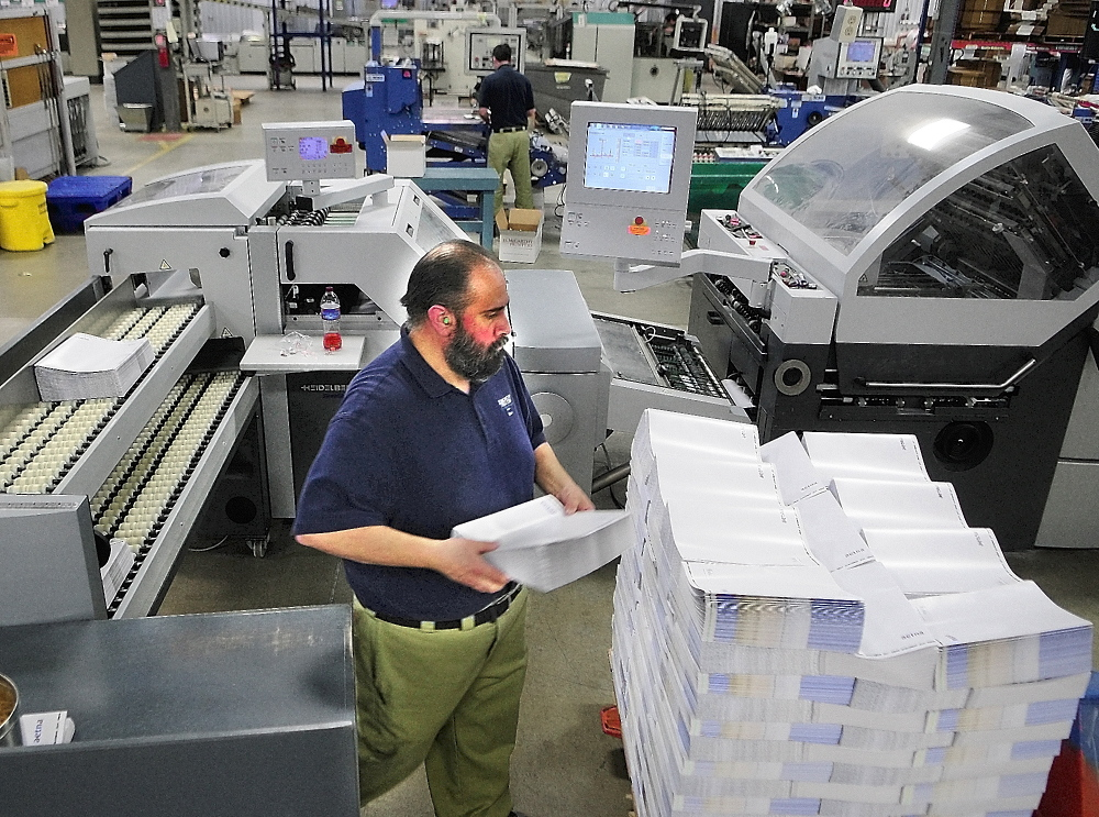 Health care: Folder operator Reno Cyr works on Thursday at J.S. McCarthy Printers in Augusta.