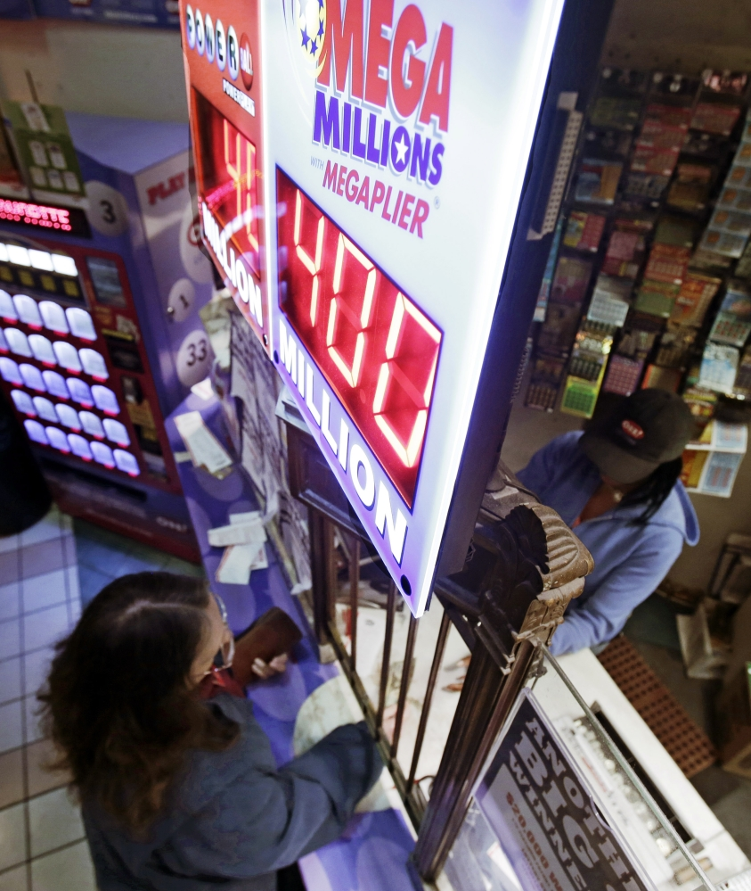 A woman buys Mega Millions lottery tickets at The Lottery Shop Thursday, Dec. 12, 2013, in Cleveland. Mega Millions, the lesser known lottery game alongside Powerball, is stepping up to the plate with an estimated $400 million jackpot for Friday's drawing, an amount that comes less than two months after a major game revamp that is supposed to create bigger jackpots and open potential playersí wallets. The jackpot is the fifth largest ever in U.S. history and the second largest in Mega Millions history, trailing behind the $656 million Mega Millions jackpot in 2012.