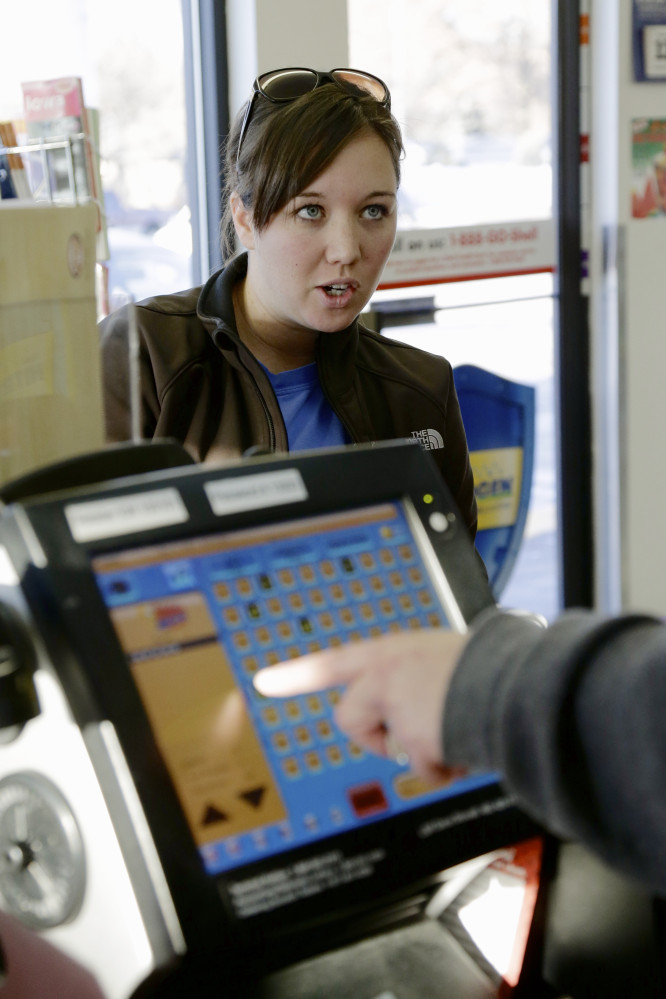 Customer Staci McDonnell dictates her Mega Millions numbers to a store clerk as she purchases lottery tickets at the Speedee Mart convenience store in Gretna, Neb., Thursday, Dec. 12, 2013, where someone bought a multi-million dollar winning Powerball lottery ticket from the previous day's drawing. Lottery officials behind Mega Millions say the lesser known game alongside Powerball, is grabbing some attention with an estimated $400 million jackpot for Friday's drawing that comes less than two months after a major revamp to the game.