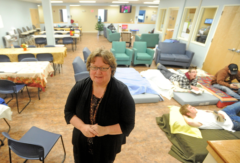 filled: Betty Palmer, executive director of the Mid-Maine Homeless Shelter in Waterville, stands in the day room that doubles as an over-flow sleeping area when the shelter is at or above capacity. Some people were already using the space Friday and Palmer expected the shelter to be over-flowing with the onset of a bitter cold snap.
