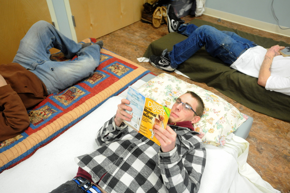 overflow: Brian Gillespie, 20, reads from his floor mat bed in the over-flow area at the Mid-Maine Homeless Shelter on Friday. Gillespie has been at the shelter for about 30 days and will be sharing the over-flow space with an increased population due in part to the bitter cold temperatures.