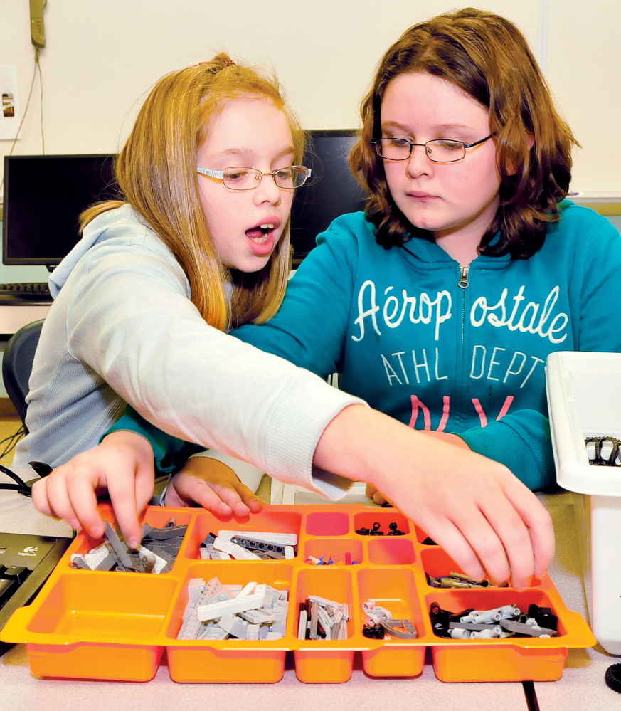 ON LEGO: Clinton Elementary School students Amber Wescott, left, and Haley Trahan select Lego pieces to construct one of Santa's reindeer during a project at the school this week.