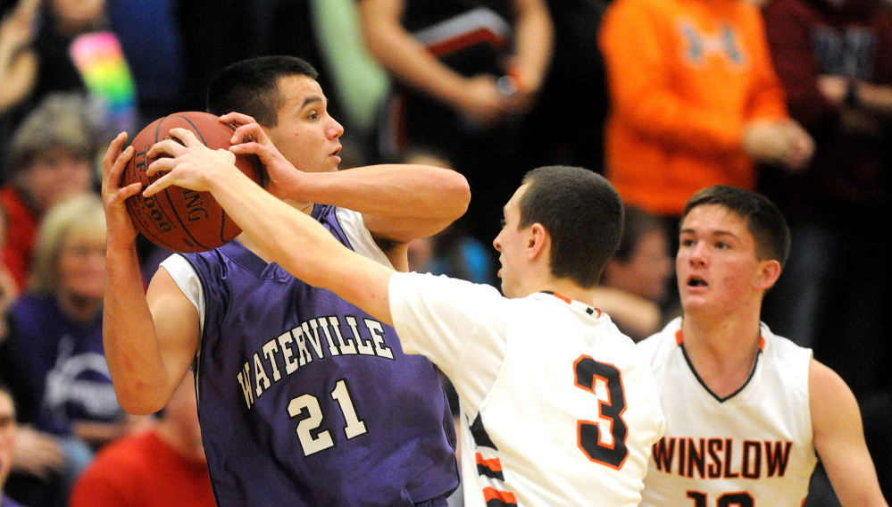 HIGH SCHOOL BASKETBALL: Winslow High School's Trevor Lovely, 3, center, tries to steal the ball from Waterville Senior High School's Chris Hale, 21, in the first quarter in Winslow on Saturday. Winslow's Connor Wildes, 12, is seen in the background.
