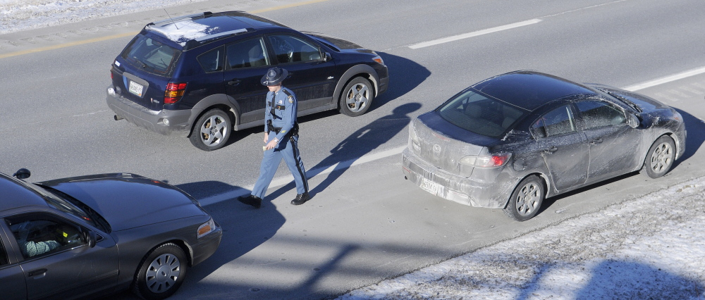 SAFETY FIRST: A car drives past Maine State Trooper Chris Rogers during a traffic stop Thursday in West Gardiner. Several State Police cruisers have been struck while parked at accidents this year, compelling police to remind drivers that they must slow down and pull over when approaching emergency vehicles.