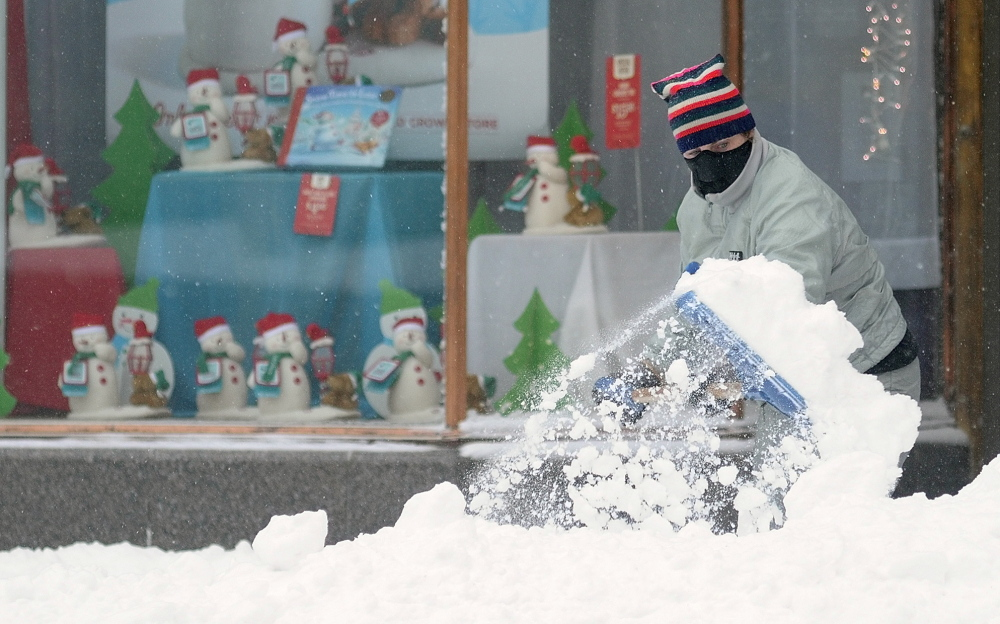 WINTER CHORE: Stacy Gervais shovels snow off the sidewalk in front of her Water Street businesses, Stacy's Hallmark and The Looke at Stacy's on Sunday in Augusta.