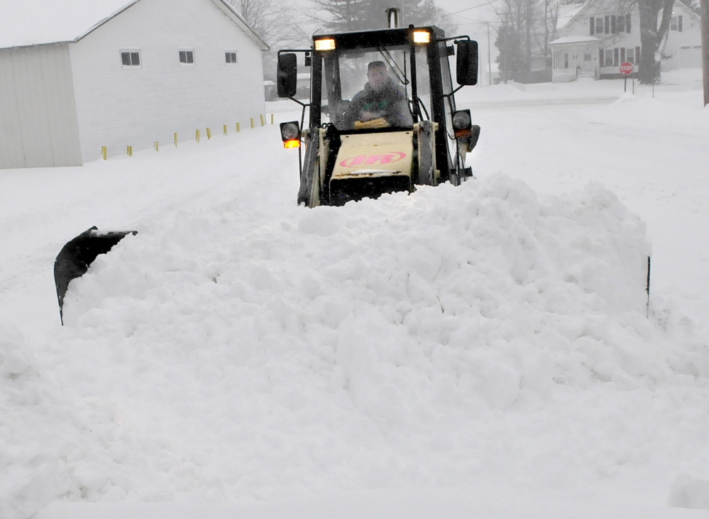 MAKING MOUNTAINS: Dan Misner II of Misner Lawn Care creates a mountain of snow while plowing in Fairfield during the snowstorm on Sunday.
