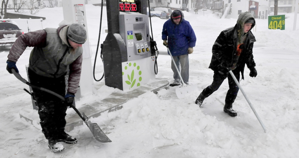 BUSY: Workers with Goodall Landscaping company kept busy shoveling and plowing during the snowstorm on Sunday. Cleaning up around gas pumps at the Cumberland Farms store in Waterville are, from left, Chris Loder, Frank Condon and John Wilcox.