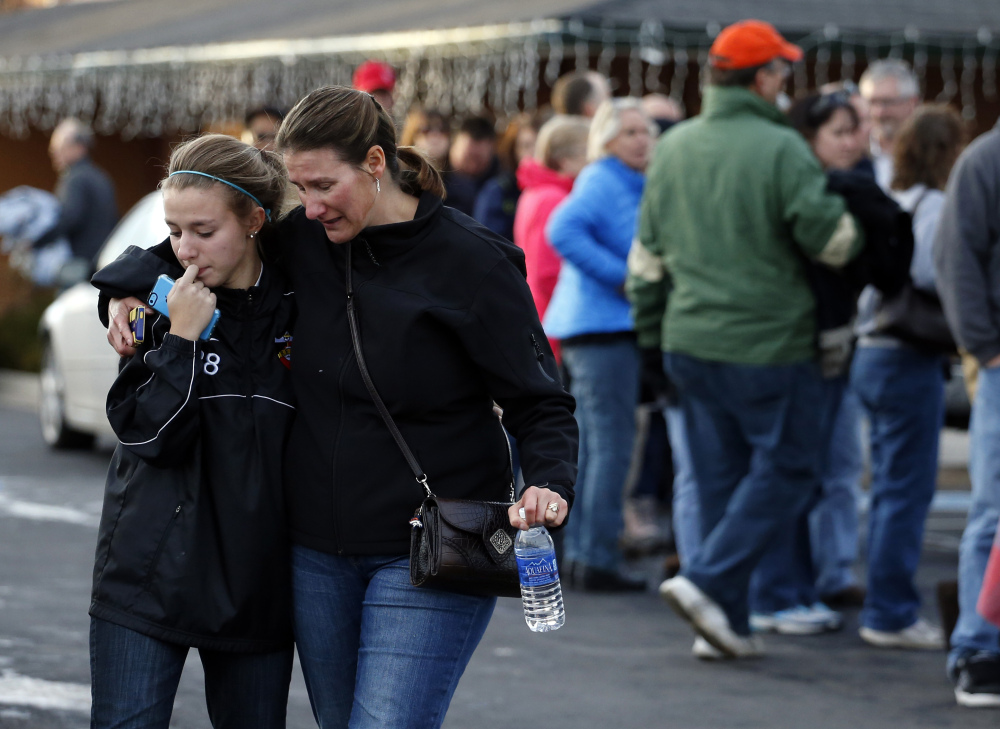 A parent picks up her daughter at a church where students from nearby Arapahoe High School were evacuated to after a shooting on the Centennial, Colo., campus Friday, Dec. 13, 2013. Arapahoe County Sheriff Grayson Robinson said the shooter shot two others at the school, before apparently killing himself.