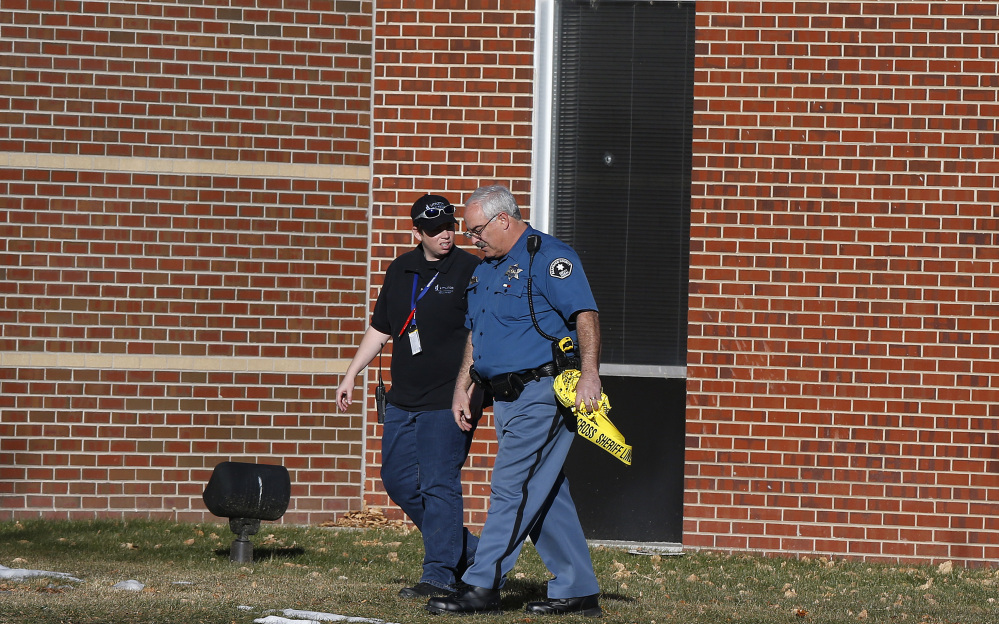 A security officer and a sheriff's deputy walk together, three days after a shooting attack at Arapahoe High School in Centennial, Colo., Monday, Dec. 16, 2013. During the attack, the shooter shot a classmate in the head at close range with a shotgun, before killing himself.